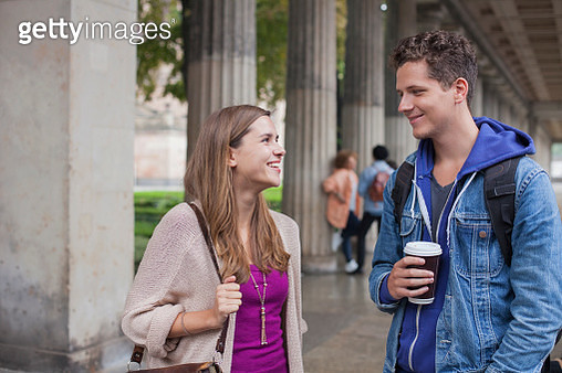 Smiling young friends talking while standing against columns - gettyimageskorea