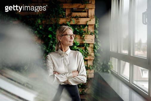 Businesswoman in green office looking out of window - gettyimageskorea