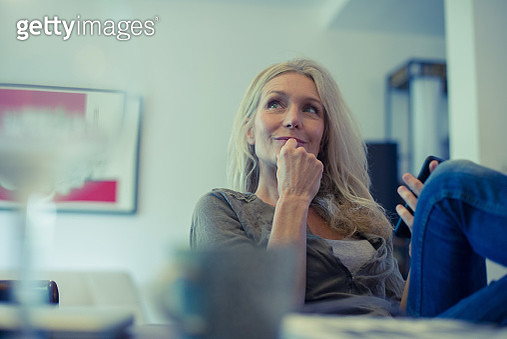 Mature woman using smartphone at home - gettyimageskorea