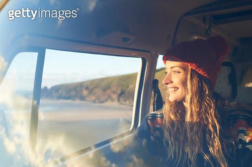 Woman looking out of camper van window. - gettyimageskorea