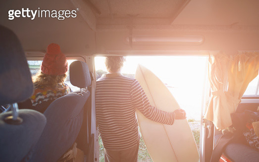 Surfing couple look out to sea from camper van. - gettyimageskorea