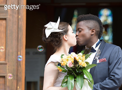 Woman and man are kissing at their marriage ceremony. - gettyimageskorea
