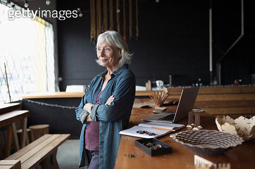 Pensive senior female entrepreneur looking away at laptop - gettyimageskorea