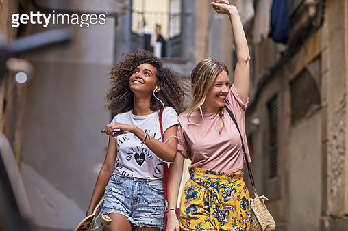 Two young women friends having fun sharing music in the street - gettyimageskorea