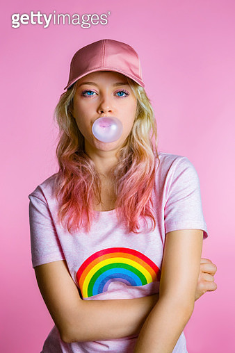 Portrait of cool young woman with bubble gum in front of pink background - gettyimageskorea