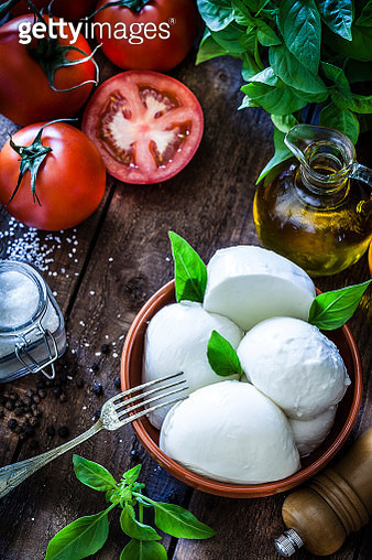Mozzarella cheese in a brown clay bowl shot from above on rustic wooden table. On the table all around the bowl are ingredients for preparing Caprese salad like tomatoes, olive oil, basil, pepper and salt. Low key DSRL studio photo taken with Canon EOS 5D - gettyimageskorea