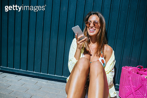 Woman with summer clothes using mobile phone - gettyimageskorea