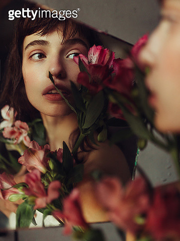Young woman reflected in mirror with flowers - gettyimageskorea