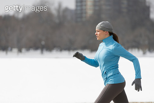 Young Woman Running in Snowy Park with snow in profile - gettyimageskorea