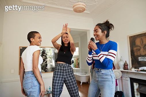 Female friends singing and dancing in bedroom - gettyimageskorea