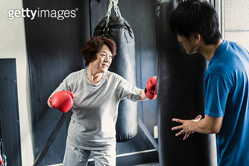 Senior adult woman training at boxing gym with coach - gettyimageskorea