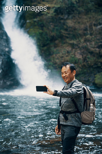 Senior man taking a selfie with a smart phone in front of a waterfall while hiking in a forest - gettyimageskorea