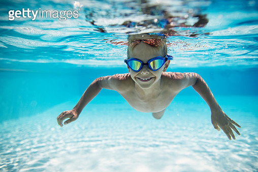 Cute little boy swimming underwater in pool - gettyimageskorea