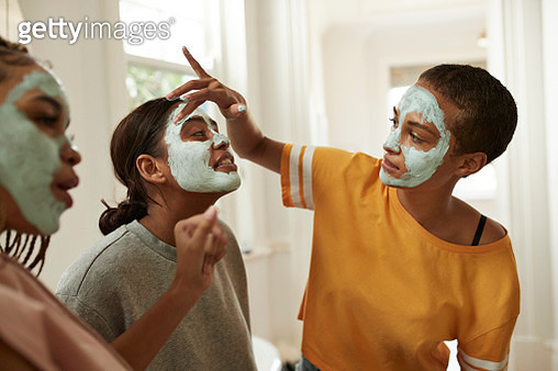 Woman looking at female friend spreading facial cream with fingers in bathroom at home - gettyimageskorea