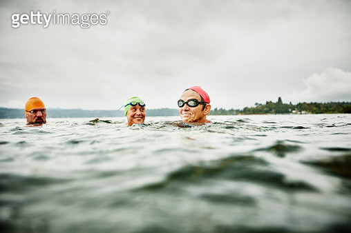 Smiling group of mature swimmers resting during open water swim - gettyimageskorea
