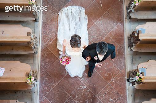 Newlywed couple walking on tiled floor in church - gettyimageskorea