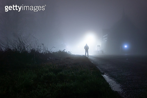 A man standing next to a church, underneath a street light, on a spooky, scary, rural, country road. On a foggy winters night - gettyimageskorea