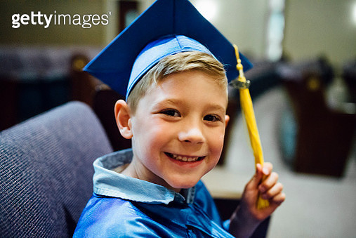Portrait of happy boy in graduation gown siting on chair - gettyimageskorea