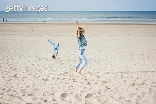 Mother and daughter having fun, cartwheeling on the beach - gettyimageskorea