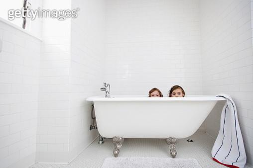 Portrait of two young girls peeking over bath - gettyimageskorea