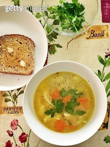 Homemade poached chickens and vegetable soup and a piece of brown toasted bread with butter - gettyimageskorea