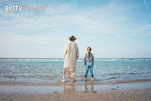 Mother and daughter standing on the beach, looking at the sea, rear view - gettyimageskorea