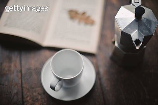 White coffee cup and saucer with espresso maker and open book on wooden table - gettyimageskorea