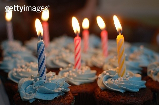 Close-Up Of Illuminated Candles On Cupcakes - gettyimageskorea