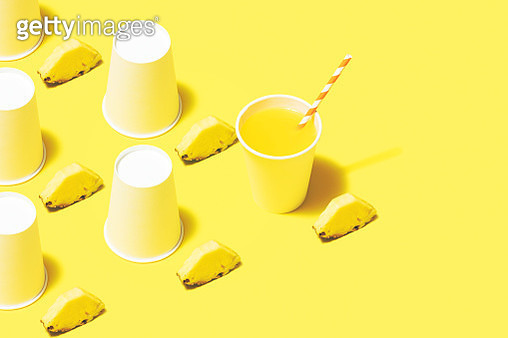 Disposable paper cups on color background. Pineapple juice flat lay on yellow background. - gettyimageskorea