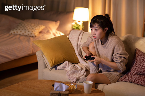 Young Chinese woman playing video game on sofa - gettyimageskorea