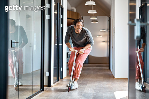 Happy young businessman enjoying while riding push scooter in office corridor - gettyimageskorea
