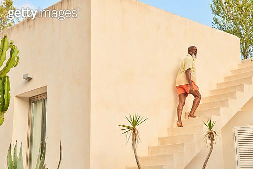 Mature man walks up stairs - gettyimageskorea