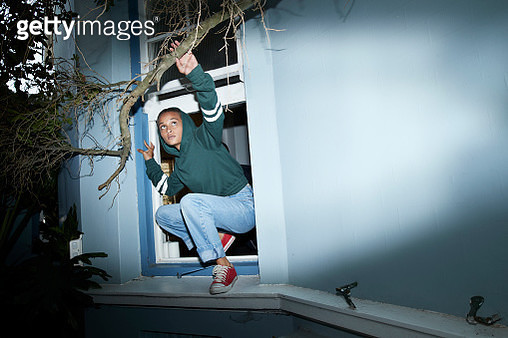 Woman sneaking out of house window - gettyimageskorea