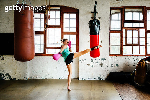 Female muay thai boxer during training session practicing kicks on a sandbag - gettyimageskorea