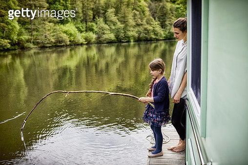 Mother and daughter on a houseboat with girl using stick as fishing rod - gettyimageskorea