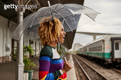 Side view of cheerful young woman enjoying while standing with umbrella at railroad station during monsoon - gettyimageskorea