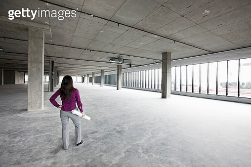 A woman architect holding architectural drawings looking out over a new raw business space. - gettyimageskorea