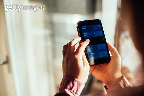 Woman checking mobile stock exchange app. - gettyimageskorea