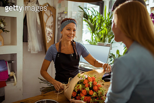 Close up of a young woman buying a bouquet from a flower store - gettyimageskorea