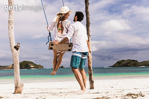 Happy woman enjoying on a swing while being pushed by her boyfriend during summer day on the beach. - gettyimageskorea