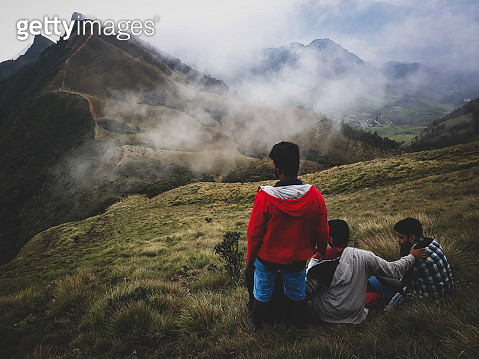 Rear View Of Male Friends On Grassy Mountain - gettyimageskorea