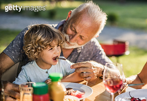Smiling grandfather feeding his small grandson during lunch in nature. - gettyimageskorea