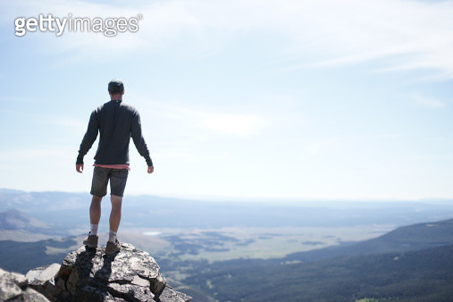 Young man on top of peak - gettyimageskorea