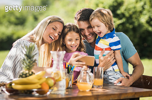 Happy family enjoying while taking a selfie with cell phone outdoors. - gettyimageskorea