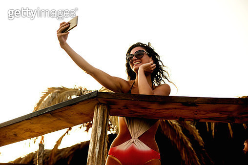 Beautiful young woman doing selfie on the beach - gettyimageskorea