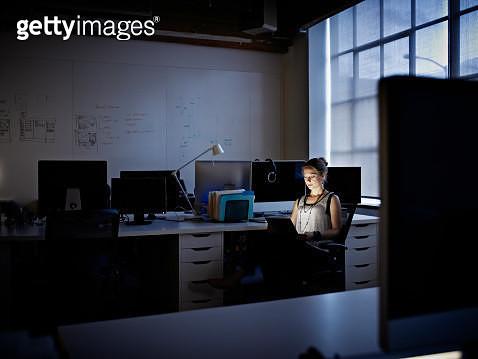 Businesswoman working on digital tablet at night - gettyimageskorea
