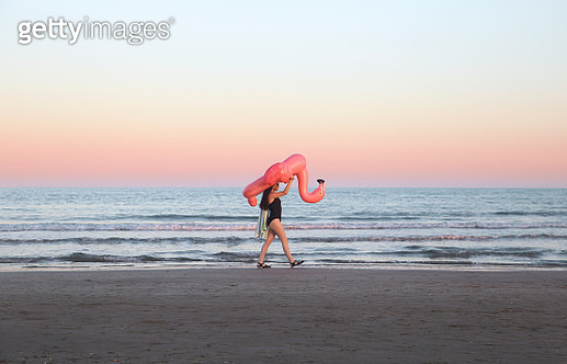 Young woman walking with inflatable pink flamingo on the beach at sunset - gettyimageskorea