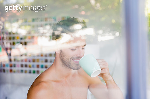 Young man having coffee seen through glass window - gettyimageskorea
