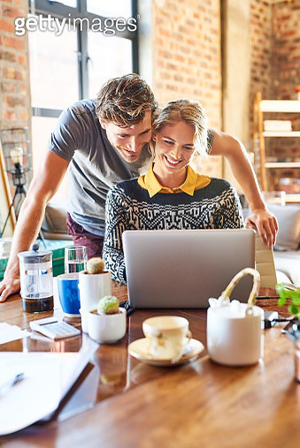 Smiling young couple using laptop at home - gettyimageskorea