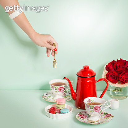 High key, high contrast, harsh shadow trendy stylized still life afternoon tea time table top shot on light green background. lady's hand picking up dessert with dessert fork. - gettyimageskorea